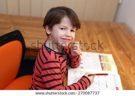 Preschooler genius boy solving math exercise at home - stock photo