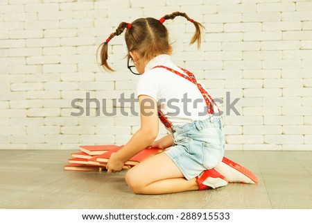 Preschooler girl with pigtails sitting on the floor - stock photo