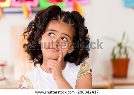 Preschooler thinking in classroom. - stock photo