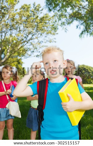 Preschoolers with books thinking at park - stock photo