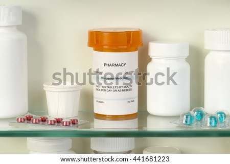 Prescription bottle on medicine cabinet shelf. Label is fictitious and created by photographer. - stock photo