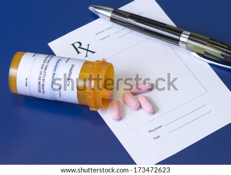 Prescription bottle, pink pills, pen, and pad on royal blue background. - stock photo