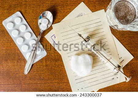 Prescription for the treatment of the disease, a tablets with glass of the water and a syringe on the table - stock photo