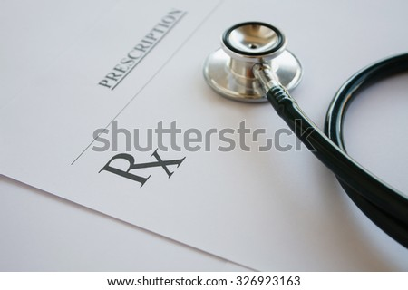 Prescription form lying on table with stethoscope. Medicine or pharmacy concept. Empty medical form ready to be used. - stock photo