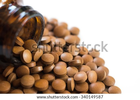 Prescription pill bottle spilling pills on to surface isolated on a white background.drug. - stock photo