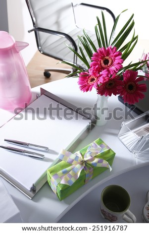 Present and flower vase on office table - stock photo