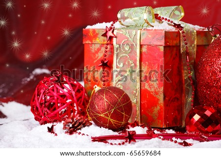 Present box and Christmas balls over red - stock photo