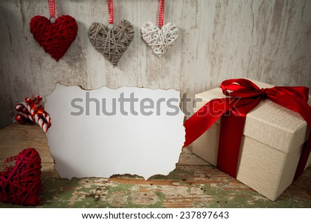 Present box and some decoration laying on a old wooden table and hanging on the wall - stock photo