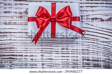 Present box red bow on vintage wooden board holidays concept. - stock photo