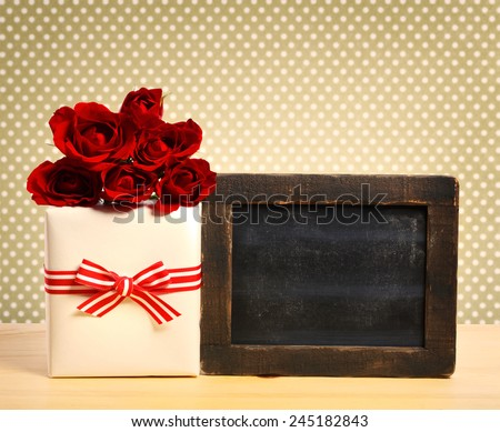 Present box with roses and blank chalkboard on polka dot background - stock photo