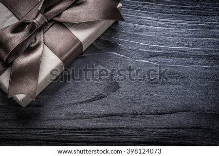 Present box wrapped in recycled paper on wooden board. - stock photo