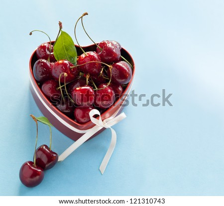 Present for Valentine's day. Red heart shaped box with sweet cherries and white ribbon on light blue background. - stock photo