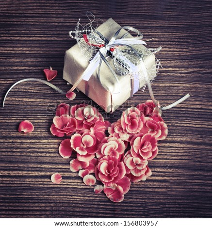 Present,gift bow with heart from petal from flowers on wooden table/valentines day background - stock photo