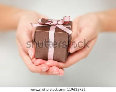Present / gift. Close up of hands holding small gift with ribbon. - stock photo