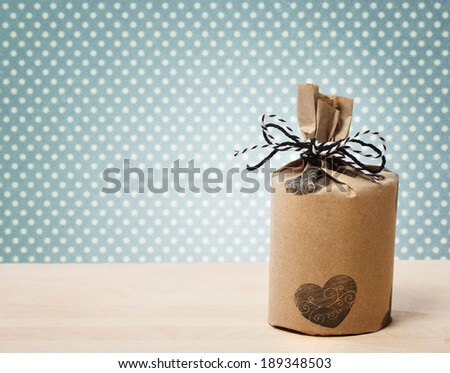 Present wrapped in a rustic earthy style on blue polka dots background - stock photo