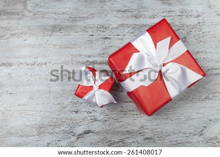 Present wrapped in red paper on a wooden background with a checkered ribbon for christmas, birthday, mother's day or valentine - stock photo