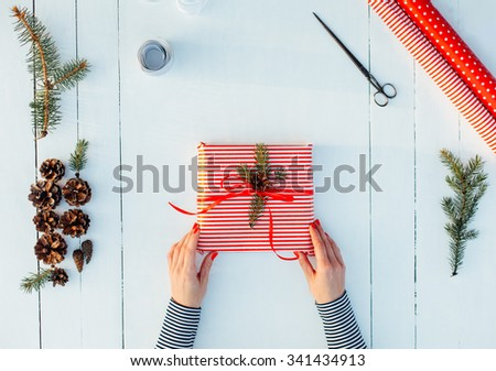 Present wrapped in red paper on a wooden background with a red ribbon for christmas, birthday, mother's day or valentine - stock photo