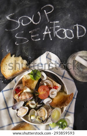 Presentation of a soup with seafood on a black background with writing - stock photo