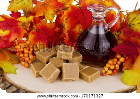 Presentation of maple syrup and sugar cream fudge on wooden plate. - stock photo