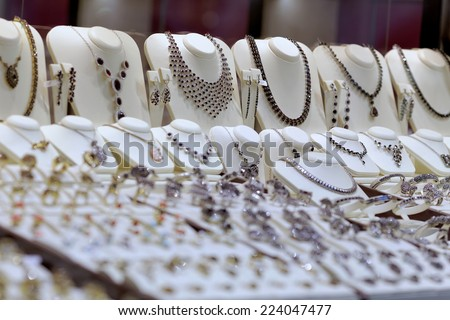 Presentation of retail showcase in jewelry store with necklaces and other jewelry  - stock photo