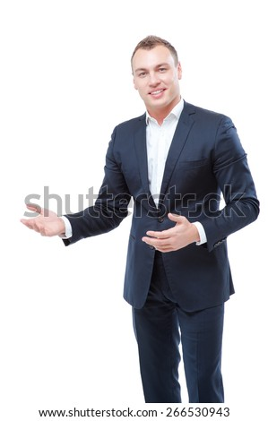 Presenting your product. Half length of happy young man in formal wear pointing copy space or gesturing welcome sign while standing isolated on white. - stock photo