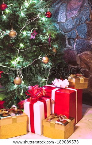 Presents boxes under the Christmas tree. Gold, red and white colours - stock photo
