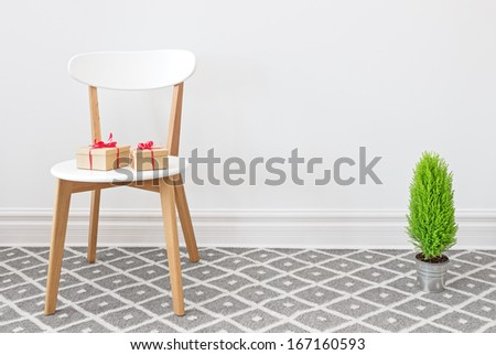 Presents on an elegant white chair, and little green cypress tree. - stock photo
