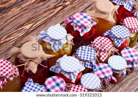 Preservation in glass jars on the old boards. Canned fruits and vegetables homemade.  - stock photo