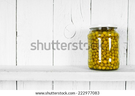 Preserved food in glass jar, on a wooden shelf. Marinaded peas - stock photo