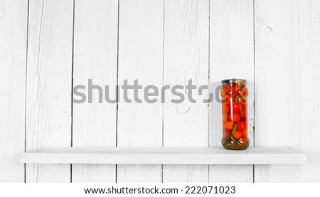 Preserved food in glass jar, on a wooden shelf. Marinaded tomatoes - stock photo