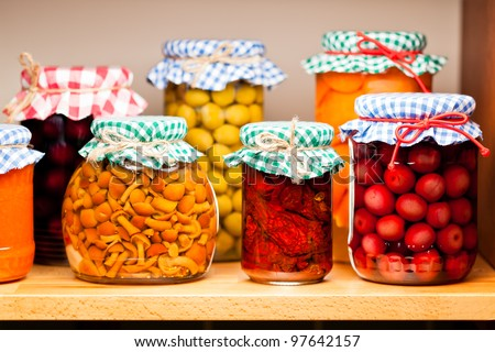 Preserved fruits and vegetables on the wooden shelf. Shallow deep of focus. - stock photo
