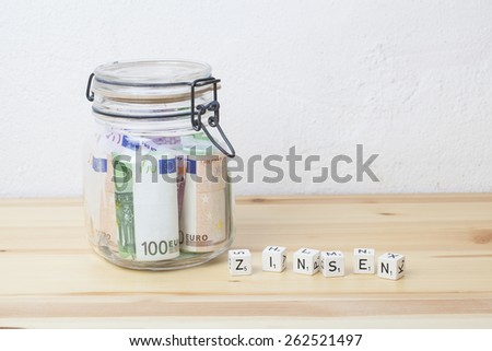 preserving glass with Euro banknotes and letter cubes with the german word Zinsen on a wooden board, financial concept for saving money and interest - stock photo