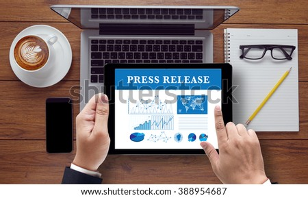 Press Release  concept on the tablet pc screen held by businessman hands, top view - stock photo
