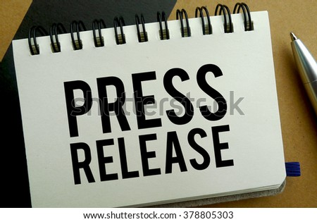 Press release memo written on a notebook with pen - stock photo
