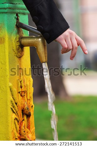 Pressing a valve to get some clear water in the well room - stock photo