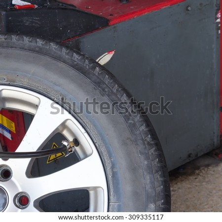 Pressure check and inflating car tire - stock photo