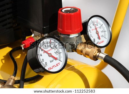 Pressure meters and compressor safety valve closeup - stock photo