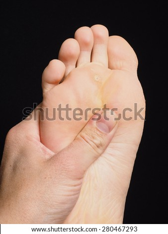 Pressure point massage under foot with thumb isolated towards black - stock photo