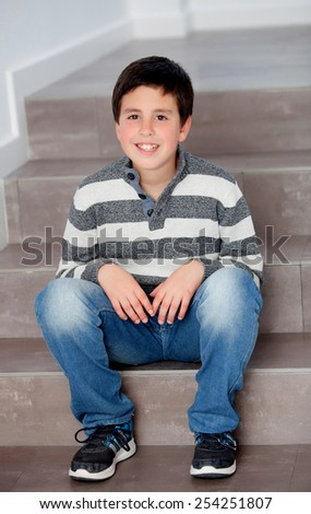 Preteen boy sitting on the stairs at home - stock photo