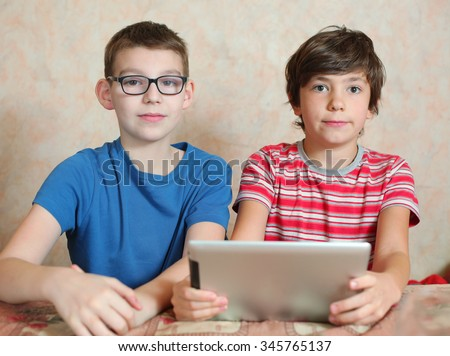 preteen boys with myopia glasses play computer games - stock photo