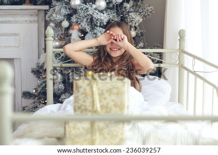 Preteen child girl wake up in her bed near decorated Christmas tree in beautiful hotel room in the holiday morning, enjoing with presents - stock photo