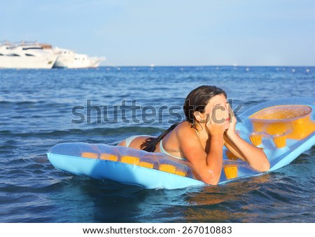 preteen girl in swimming suit with inflatable matress on the blue sea with yacht background - stock photo