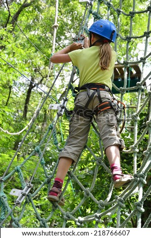 Preteen girl is climbing on the rope net at the ropes course. She is photographed on the high tree in the green forest. - stock photo