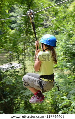 Preteen girl is zipping down at the rope parkour outdoors. She is photographed against the green forest. - stock photo