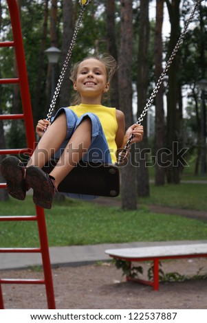 Preteen girl swinging on swing set on playground in park - stock photo