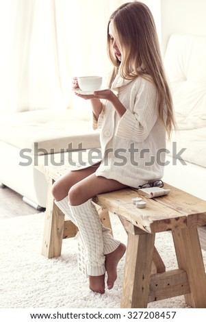 Preteen girl wearing warm knitted clothing is sitting on rustic chair on a carpet and relaxing in white living room. Winter weekend. - stock photo