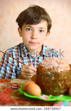 preteen handsome boy decorate easter egg and cake - stock photo