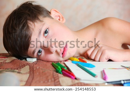 preteen handsome boy drawing with colored pencils and crayons tired falling asleep - stock photo