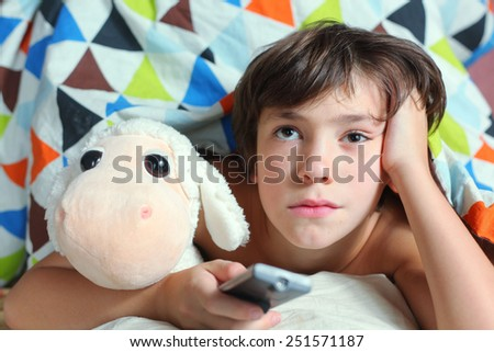 preteen handsome boy have a good time in bed watch tv - stock photo
