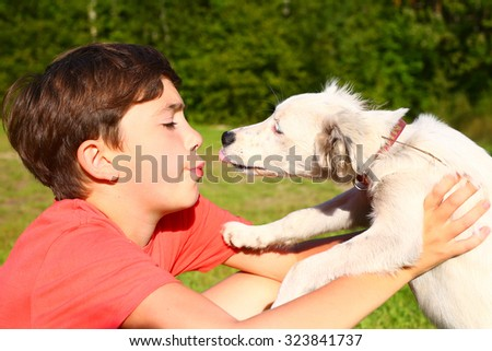 preteen handsome boy play with white puppy on the summer country background - stock photo